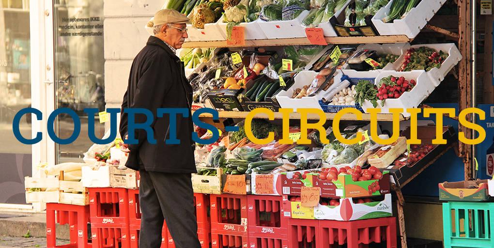 vieil homme devant un étal de fruits et légumes