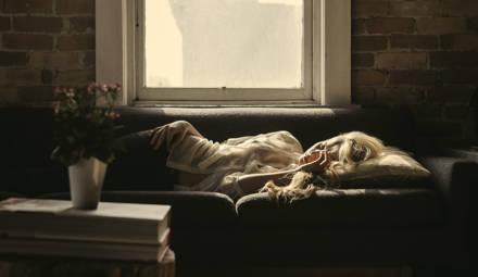 femme allongée sur un canapé à l'intérieur d'une maison