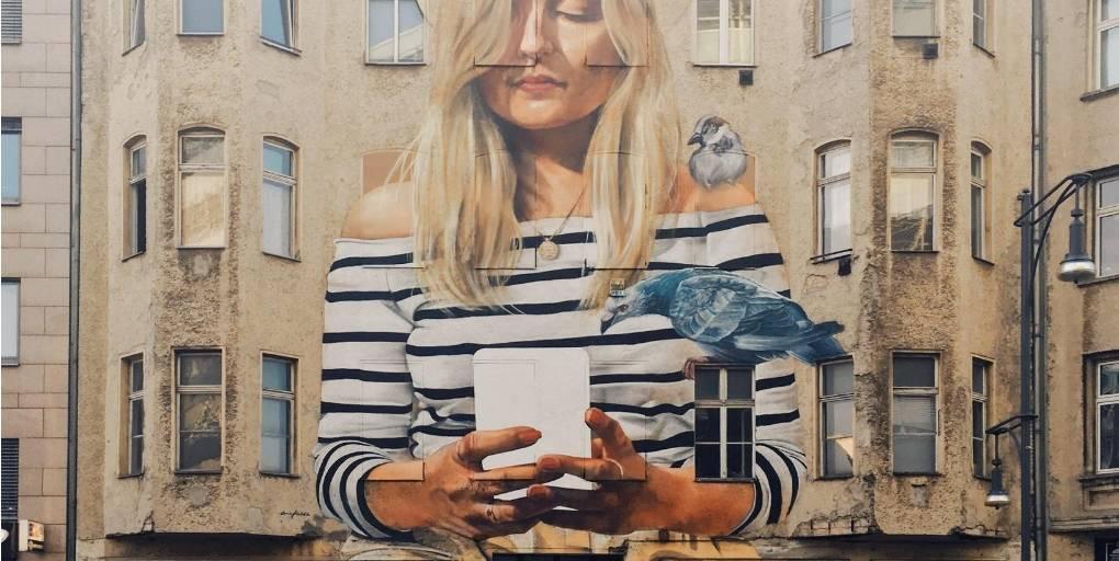 fresque murale d'une femme avec un mobile dans les mains
