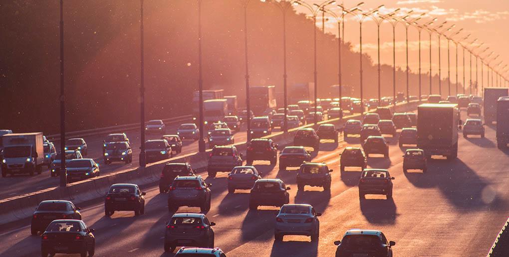 Des voitures sur une route au coucher du soleil