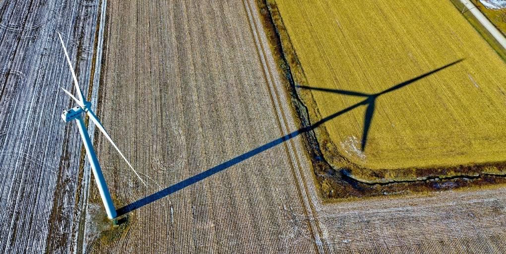 une éolienne et son ombre sur un champ