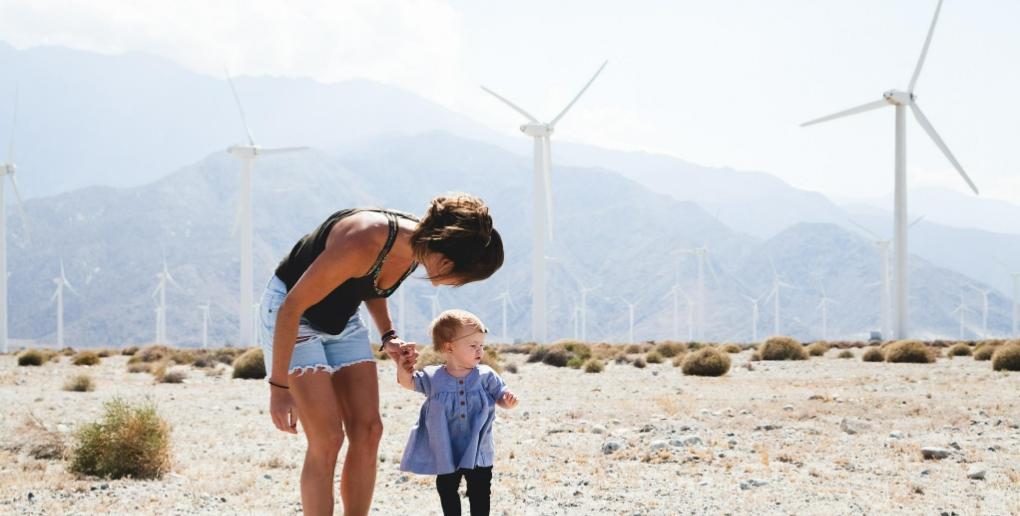 Une femme et un enfant près d'un champ d'éoliennes.
