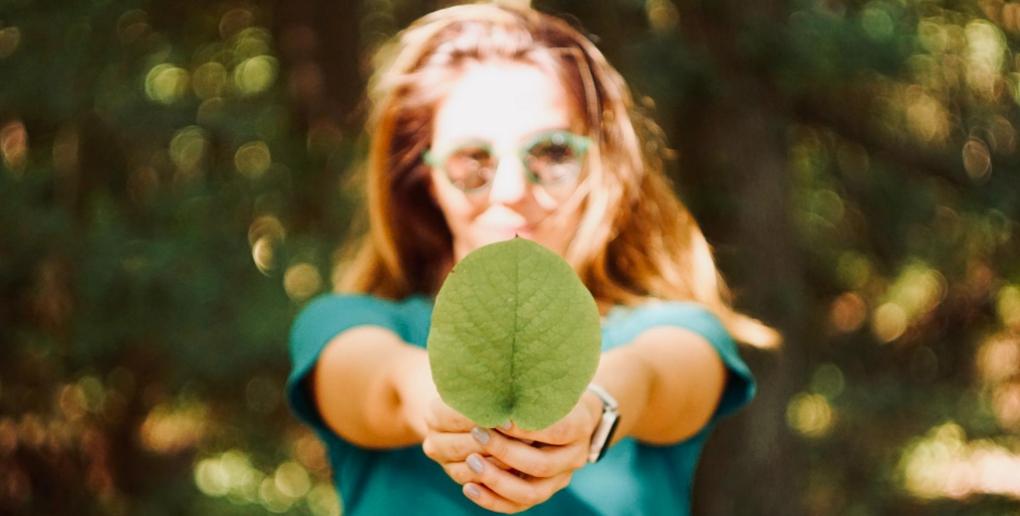 jeune femme tenant une feuille d'arbre dans ses mains