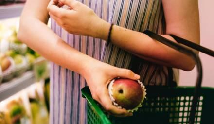 une femme met une pomme dans un panier à courses