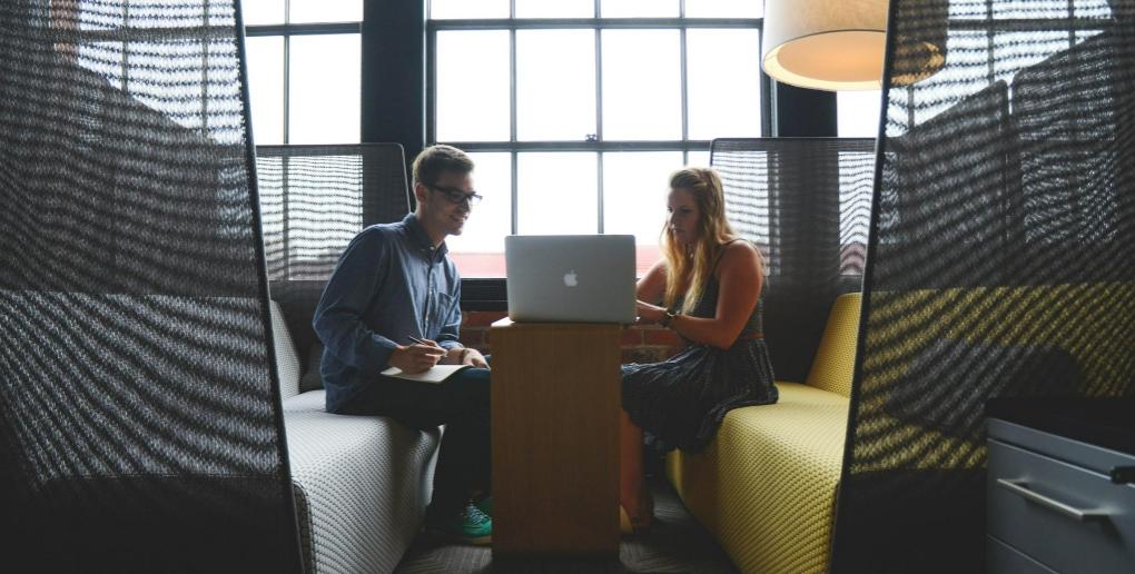 un homme et une femme devant un ordinateur de marque APPLE