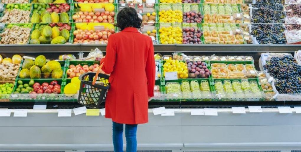 femme devant un rayon de fruits dans un supermarché