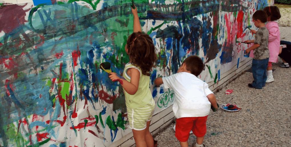 des enfants qui peignent une fresque sur un mur