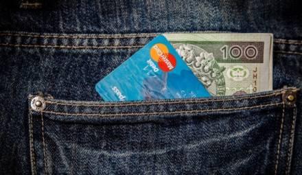 Une carte bancaire MasterCard et un billet dans une poche